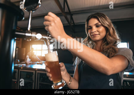 Young woman dispensing beer in a bar from metal spigots. Beautiful female bartender tapping beer in bar. - Stock Photo