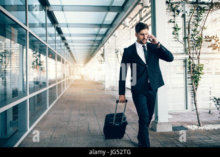 Handsome young man on business trip walking with his luggage and talking on cellphone at airport. Travelling businessman - Stock Photo
