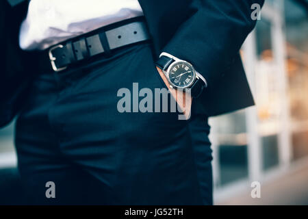 Close up of a business man's hand wearing a watch. Hand in pocket with wrist watch. - Stock Photo