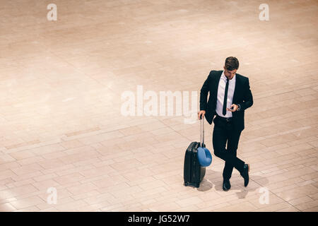 Top view shot of young businessman standing at airport terminal with suitcase and using mobile phone. Business traveler - Stock Photo