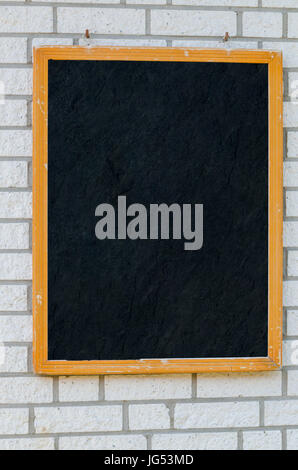 Empty large slate boards with wooden frame on a stone wall. - Stock Photo