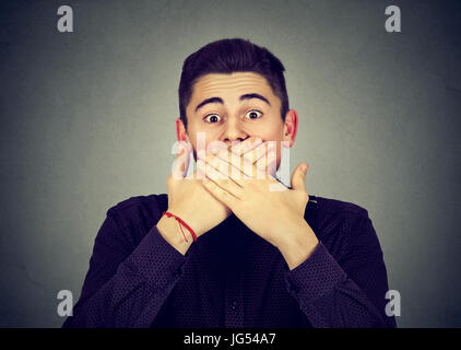 Scared man covering mouth with hands - Stock Photo