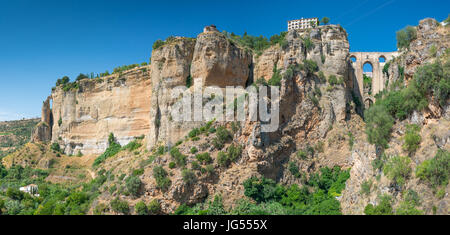 Ronda Panorama with countryside foreground showing the Parador,  Puente Nuevo and El Tajo Gorge against a bright - Stock Photo