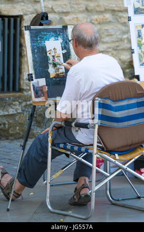RONDA, SPAIN - JUNE 2017: A Street artist at work painting the many beautiful buildings within Ronda, Spain - Stock Photo