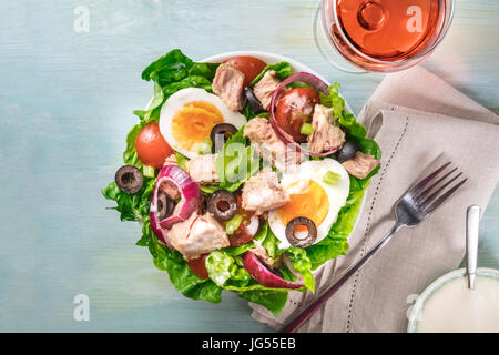 Overhead photo of a plate of salad with canned tuna, boiled eggs, green lettuce leaves, onions, black olives, and - Stock Photo
