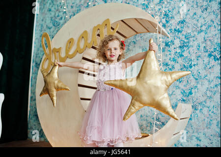 Beautiful little girl in a dress posing next to wooden moon decoration with golden star pillows. - Stock Photo