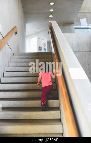 A little girl climbs a flight of stairs in an art gallery. - Stock Photo