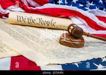 The United States Constitution rolled up on an American flag with a gavel in the foreground. Room for copy along - Stock Photo