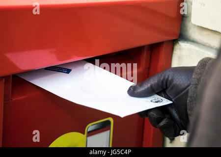 Sending a letter. Putting it to the red post box - Stock Photo