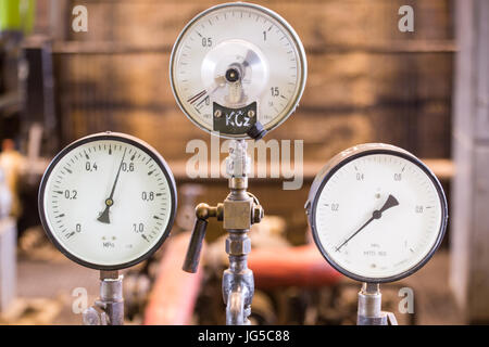 Vintage mining winch empowered by steam engine.Gauges and flywheel. - Stock Photo