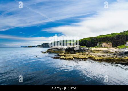 Coastal rocks with a very calm sea and blue sky, Northern Ireland - Stock Photo