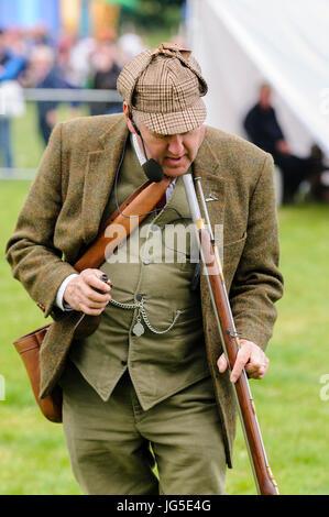 A man dressed in green Irish Lovat tweed jacket, deerstalker hat, waistcoat and trousers, looks down the barrel - Stock Photo