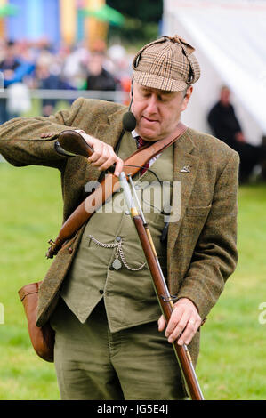 A man dressed in green Irish Lovat tweed jacket, deerstalker hat, waistcoat and trousers, loads his flintlock rifle - Stock Photo
