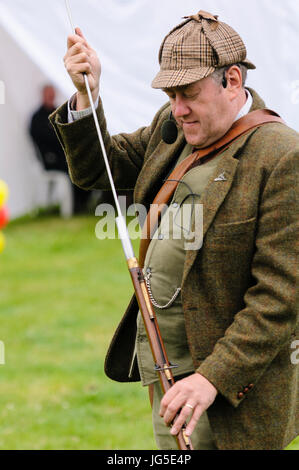 A man dressed in green Irish Lovat tweed jacket, deerstalker hat, waistcoat and trousers, uses a rod to pack wadding - Stock Photo