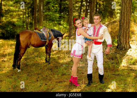 a Ukrainians Mom and Dad and daughter in the woods with a horse - Stock Photo