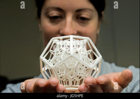 Woman holds complex 3-dimensional object produced by Selective Laser Sintering (SLS). - Stock Photo