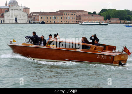 Asian tourists enjoying the ride in a water taxi along the Grand Canal, Venice, Italy - Stock Photo