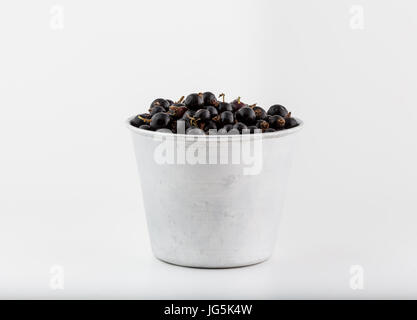 Black currant and berries stacked in ceramic and alluminum bowl, isolated on white background, fresh vegan fruits - Stock Photo