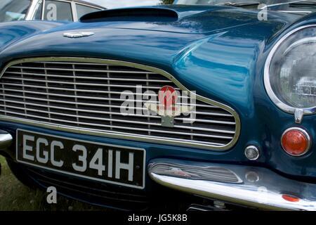 Aston Martin winged logo badge on grille of blue vintage car - Stock Photo