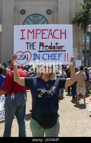 Woman holding an 'Impeach the Predator in Chief' sign at the Impeachment March in San Diego on July 2, 2017 to protest - Stock Photo