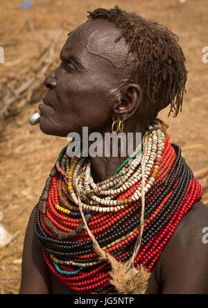 Portrait of an old Nyangatom tribe woman in a village with a chin decoration, Omo Valley, Kangate, Ethiopia - Stock Photo