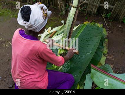 A Dorze woman prepares unleavened bread made from the false banana tree, Gamo Gofa Zone, Gamole, Ethiopia - Stock Photo