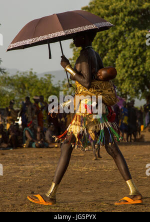 Woman carrying her baby on her back with an umbrella during the fat men ceremony in Bodi tribe, Omo valley, Hana - Stock Photo