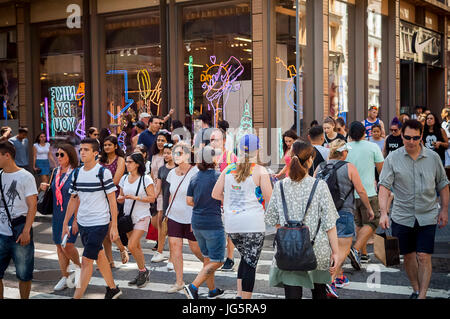 Hordes of shoppers cross Spring Street at Broadway. in Soho in New York on Saturday, June 24, 2017. (© Richard B. - Stock Photo