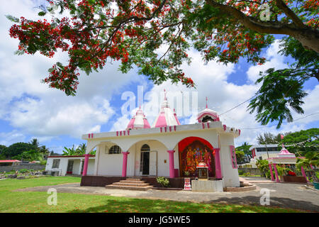 Grand Baie, Mauritius - Jan 10, 2017. A Hindu temple with flamboyant tree in Port Louis, Mauritius. According to - Stock Photo
