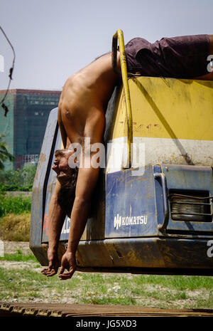 Delhi, India - Mar 9, 2017. A young worker doing exercise on the bulldozer in Delhi, India. Delhi is the fifth most - Stock Photo