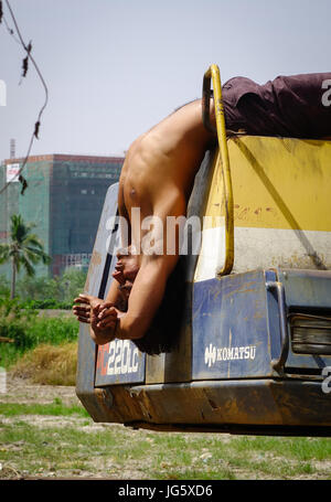 Delhi, India - Mar 9, 2017. A young worker doing yoga exercise on the bulldozer in Delhi, India. Delhi is the fifth - Stock Photo