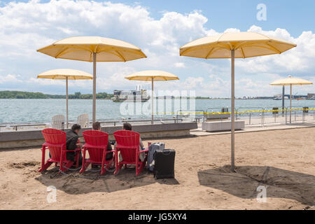 Toronto, Canada - 26 June 2017: Three men sitting next to travel backs on Toronto Beach and looking at Ontario Lake - Stock Photo