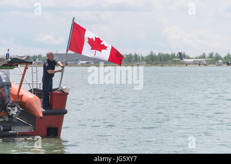 Toronto, Canada - 26 June 2017: Fireman raising a canadian flag at Toronto Harbourfront - Stock Photo