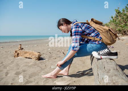 portrait of a lady sitting on the wood in front of wide beach take off her black canvas shoes and roll her jeans - Stock Photo
