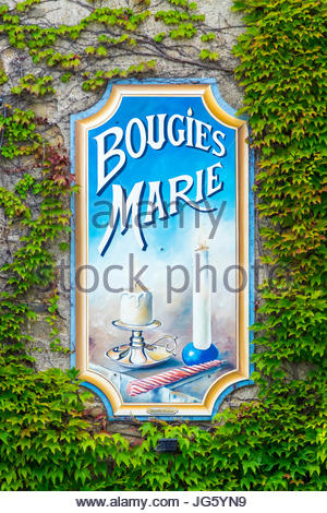 France, Brittany (Bretagne), Morbihan department, Rochefort-en-Terre. Painted advertisement for Bougies Marie candlemakers. - Stock Photo