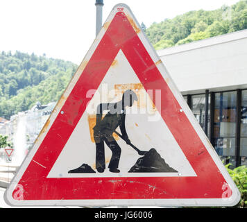 A rusty triangular sign warning of roadworks ahead with a modern city building in the background - Stock Photo