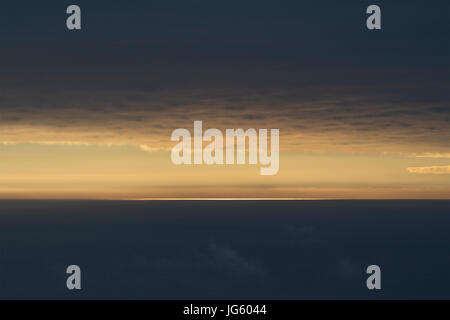 Golden afternoon light on the horizon among the darkness of the storm. - Stock Photo
