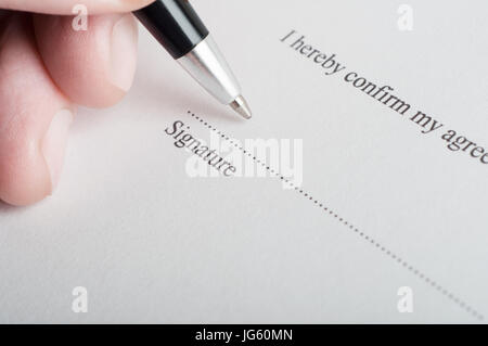 Close up (macro) shot showing fingers of a male hand, holding a pen, poised to sign on the dotted line of a legal - Stock Photo