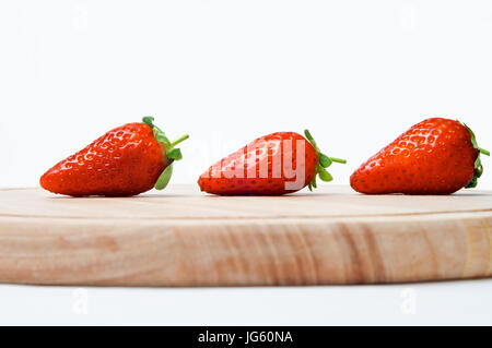 A line of three red strawberries with leaves and short stalks intact, shot sideways at eye level, on a wooden chopping - Stock Photo