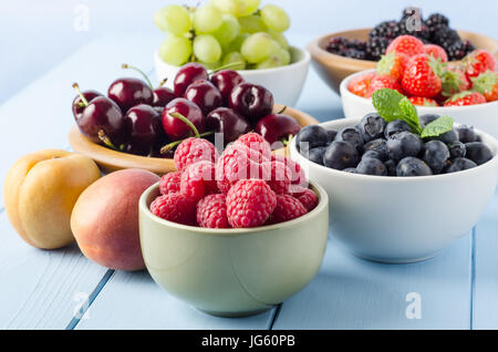 A selection of different Summer fruits, in a variety of bowls on a painted blue wood planked farmhouse kitchen table, - Stock Photo