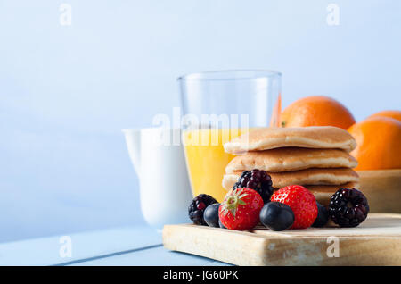 Breakfast table scene with Summer berry fruits and a stack of pancakes on an old wooden chopping board, a bowl of - Stock Photo