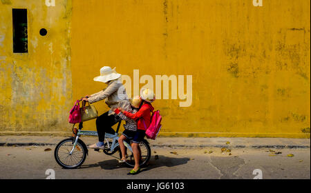 A woman rides a bike with two young children on the back in the Old Town of Hoi An, Vietnam - Stock Photo