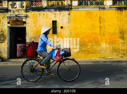A Vietnamese woman rides a bike in a street in Hoi An, Vietnam - Stock Photo