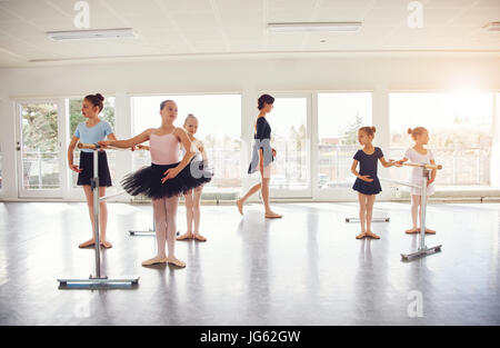 Young girls performing ballet standing and exercising in ballet class. - Stock Photo