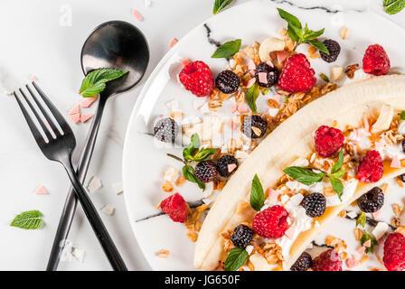 Summer fruit berry breakfast. Healthy banana split breakfast with cream cheese, raspberries, blackberries, mint, - Stock Photo