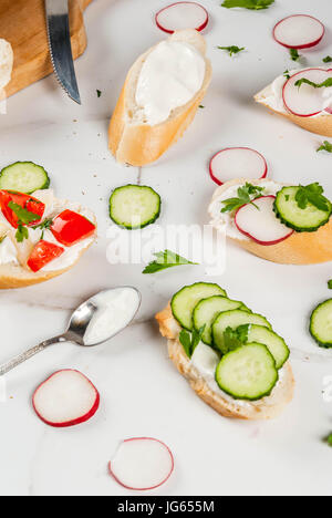 Healthy food. Spring, summer snacks. Sandwiches toast with homemade cream cheese and fresh vegetables - radish, cucumber, tomatoes, onion, pepper. On