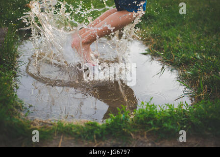 A child jumps in a mud puddle with water splashing around his feet. - Stock Photo