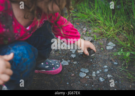 A child picks up a rock while exploring in the woods. - Stock Photo