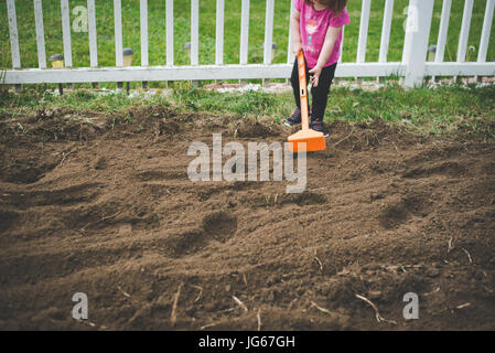 A toddler helps to hoe a garden in a backyard. - Stock Photo