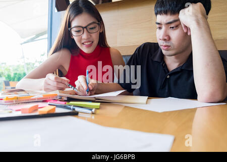 Young couple doing coursework at the table. - Stock Photo
